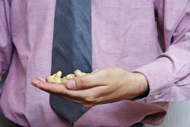 A businessman holding peanuts in his hand