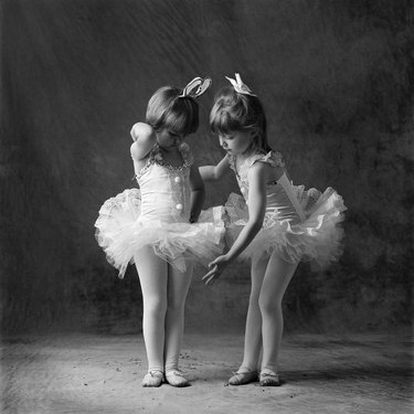 Two young caucasian ballerinas primp and get ready to dance