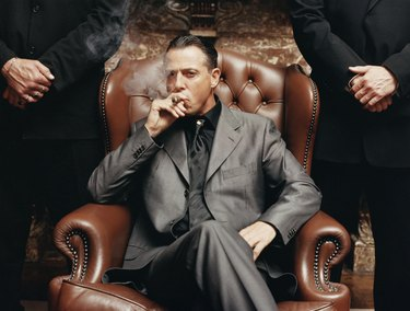 Wealthy Criminal Sitting in an Armchair Between two Bodyguards