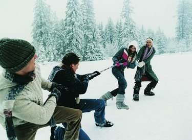 Young Couples Outdoors in the Snow Playing a Game of Tug of War