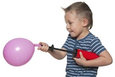 Little boy inflates a balloon
