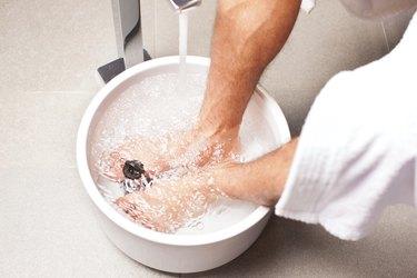 man having hydrotherapy water footbath