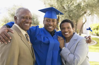Portrait of a Young Man With His Arm Around His Mother and Father at Graduation