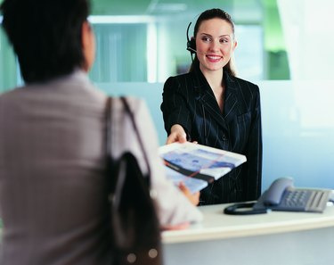 Receptionist Wearing a Headset Giving a Businesswoman a Brochure