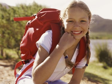 Portrait of a Girl Outdoors, Crouching Wearing a Rucksack