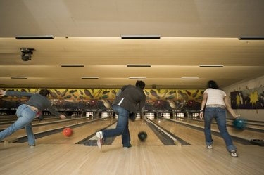 Rear view of three people bowling at a bowling alley