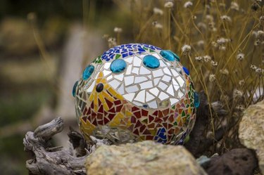 Bowling ball mortared with ceramic tiles and broken mirrors in outdoor garden. Turquoise glass buttons in sea of mirrors. Deep blue ceramic chips on top. Yellow and red ceramic chips create pattern on lower front side. Driftwood chunk lower left and dried flowers behind right.