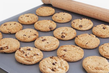Chocolate chip cookies  on a baking tray with a rolling pin
