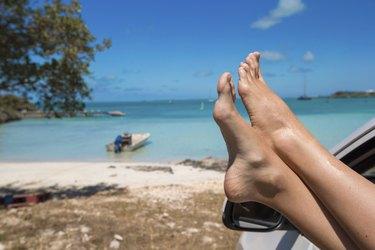 Female feet from window of car on background tropical beach