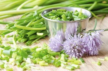 Chopped chives and flowers on bamboo board