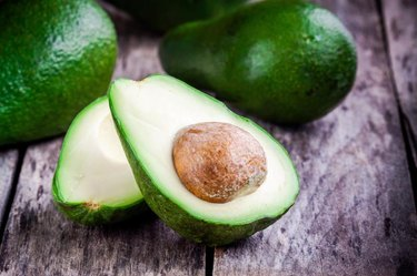 fresh raw avocado on a rustic wooden table