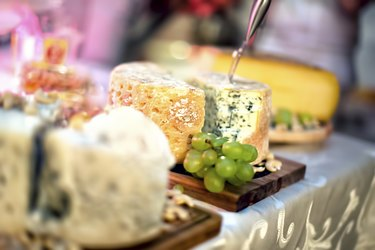 Plate with pieces of various types of cheese, white grapes