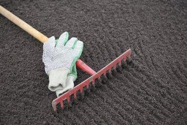 Garden rake and gloves on leveled soil