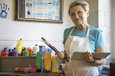 """""""Mature woman in art classroom, holding brushes and paper, portrait"""""""