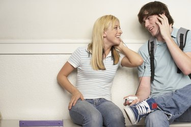 Teenage boy and a teenage girl sharing earphones