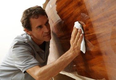 Man polishing boat in workshop
