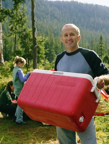Father at camping site with family, carrying cooler, portrait