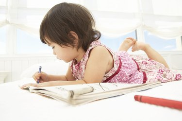Toddler girl (21-24 months) coloring on bed, side view