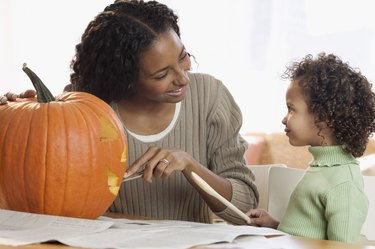 Mother carving pumpkin with her daughter