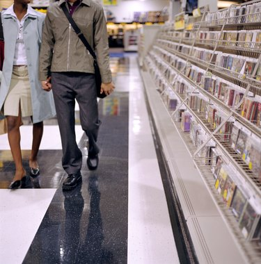Young couple holding hands in record store, low section