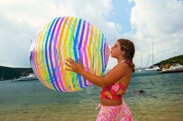 Teenage girl blowing up beach ball