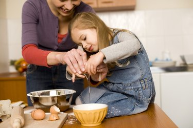 Woman and girl cooking together