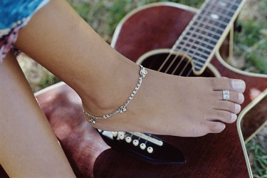 Woman's foot and guitar outdoors