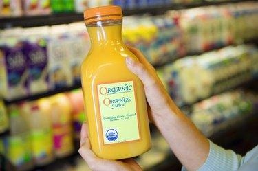 Person holding bottle of organic orange juice