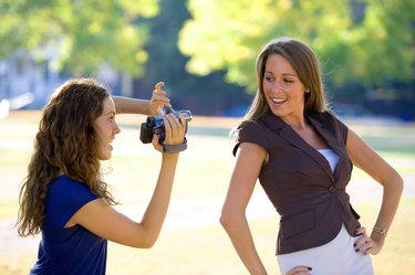 Girl filming her friend with digital camcorder outdoors