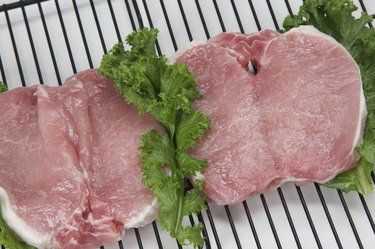 Uncooked pork chops on a grill