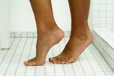 Image of person's feet standing on tiptoes on tile floor in bathroom, close-up