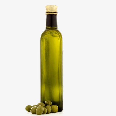 a bottle of olive oil and olives