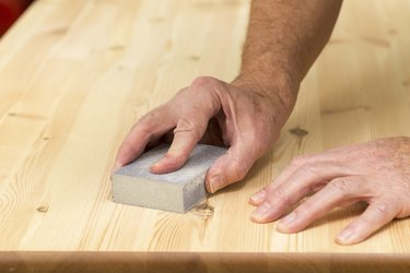 Mans hand on sanding block with pine wood