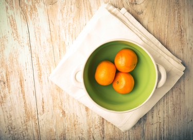 Vintage photo of tangerines in a bowl on a wood