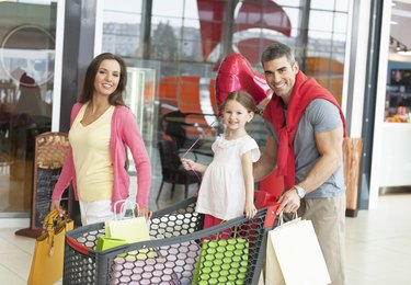 Father and mother push young daughter in shopping trolley through mall