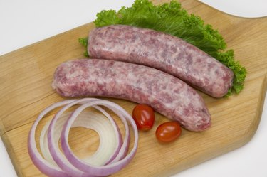 Uncooked bratwurst on a cutting board