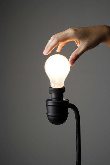 Hand on light bulb