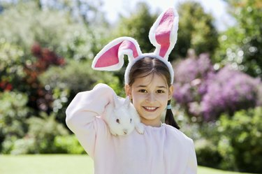 Girl in costume holding rabbit