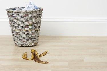 banana skin on the floor next to a bin