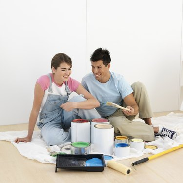 Couple sitting by paint pots in home