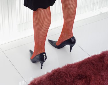Legs of woman wearing red fishnet tights and high heels