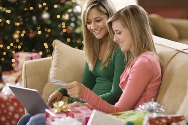 Teenage girls using laptop computer at Christmas