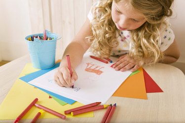 Child drawing at table