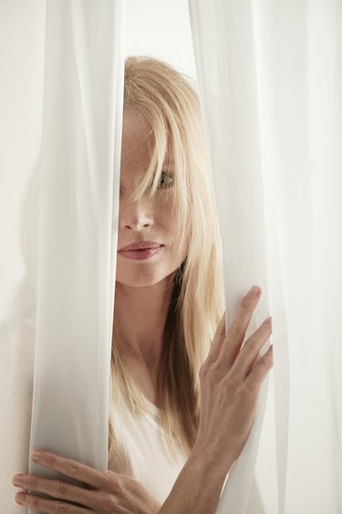 Woman looking out from behind curtains