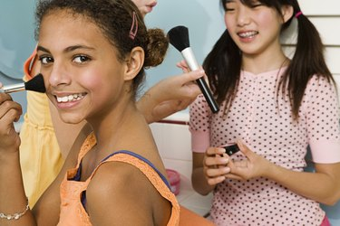 Two preteen girls applying makeup