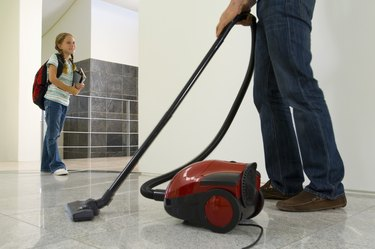 Girl watching father vacuum