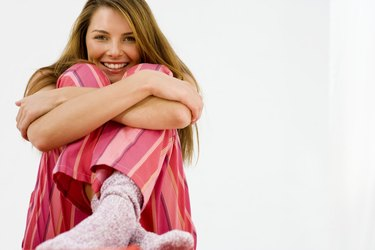 Smiling woman huddling with knees to chest