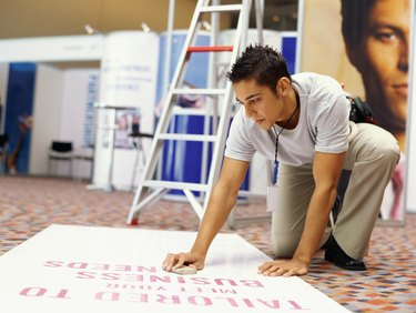 young man wiping a banner