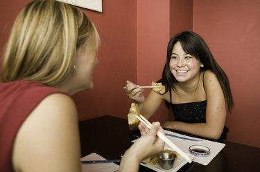 Two teenage girls (16-17), eating in restaurant
