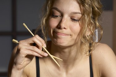 Young woman holding chopsticks, smiling